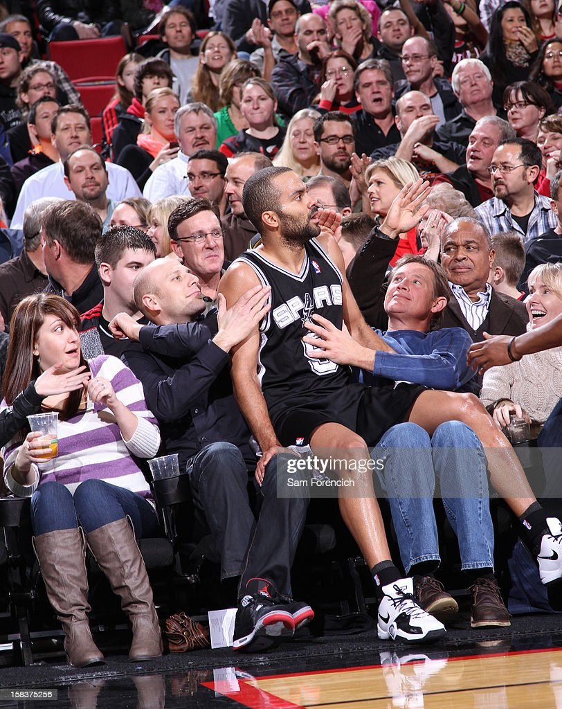 Tony Parker #9 of the San Antonio Spurs lands in the stand after trying to save a ball against the Portland Trail Blazers on December 13, 2012 at the Rose Garden Arena in Portland, Oregon.