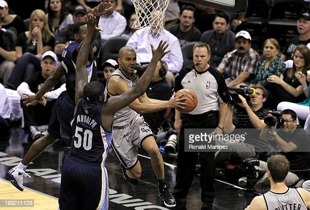 Tony Parker of the San Antonio Spurs looks to pass in the second half as he drives under the basket against Zach Randolph and Tony Allen of the...