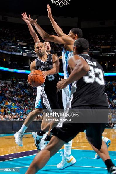 Tony Parker of the San Antonio Spurs looks to pass to teammate Boris Diaw in the lane against Greivis Vasquez and Anthony Davis of the New Orleans...