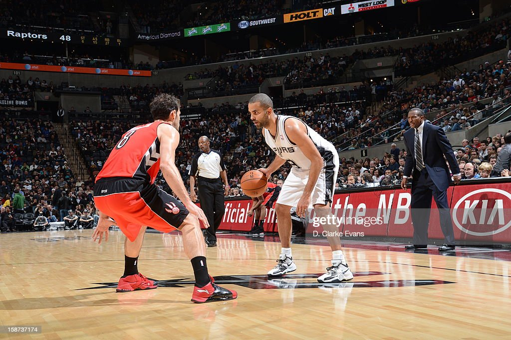 Tony Parker #9 of the San Antonio Spurs protects the ball from Jose Calderon #8 of the Toronto Raptors during the game between the Toronto Raptors and the San Antonio Spurs on December 26, 2012 at the AT&T Center in San Antonio, Texas.