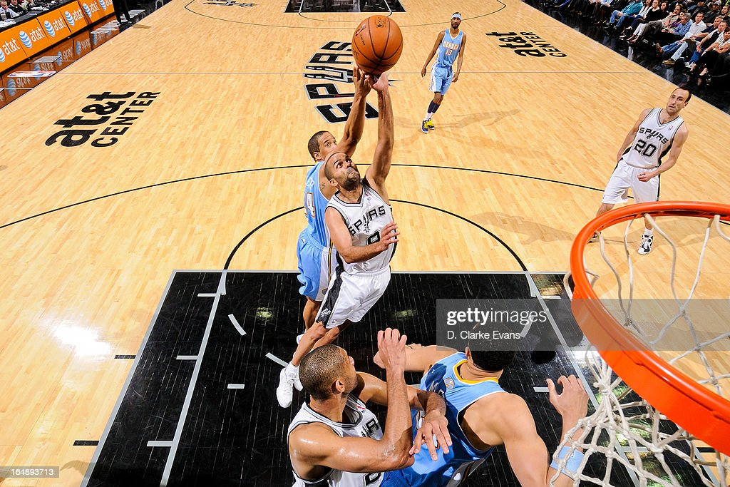 Tony Parker #9 of the San Antonio Spurs reaches for a rebound against <a gi-track='captionPersonalityLinkClicked' href=/galleries/search?phrase=Andre+Miller&family=editorial&specificpeople=201678 ng-click='$event.stopPropagation()'>Andre Miller</a> #24 of the Denver Nuggets on March 27, 2013 at the AT&T Center in San Antonio, Texas.
