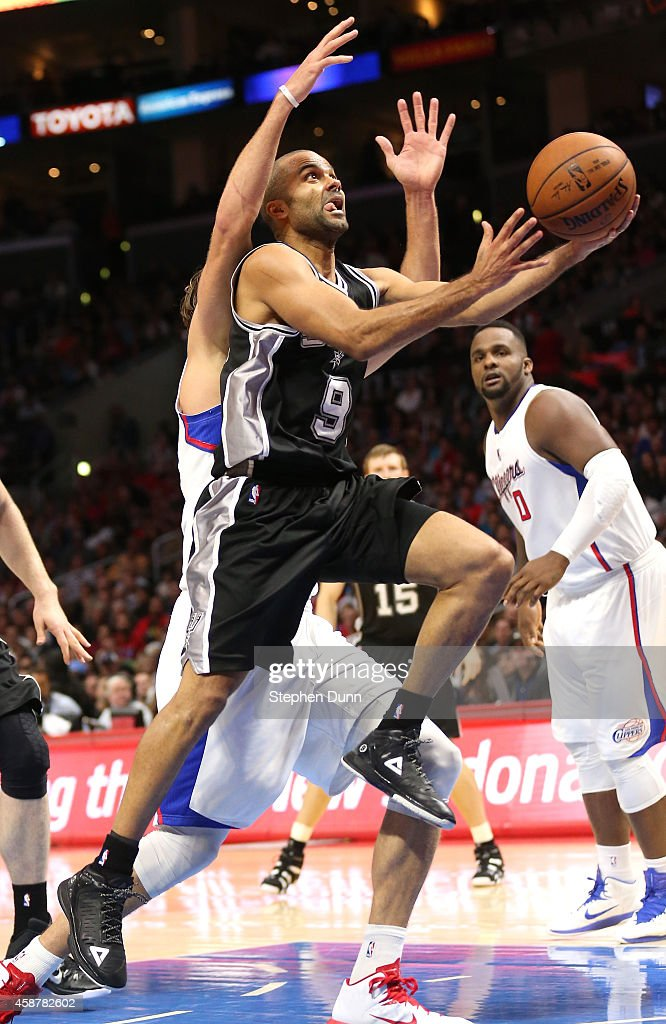 Tony Parker of the San Antonio Spurs shoots past Spencer Hawes of the Los Angeles Clippers at Staples Center on November 10 2014 in Los Angeles...