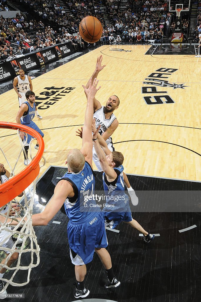 Tony Parker #9 of the San Antonio Spurs shoots the ball over Luke Ridnour #13 and Greg Stiemsma #34 of the Minnesota Timberwolves during a game played on April 17, 2013 at the AT&T Center in San Antonio, Texas.