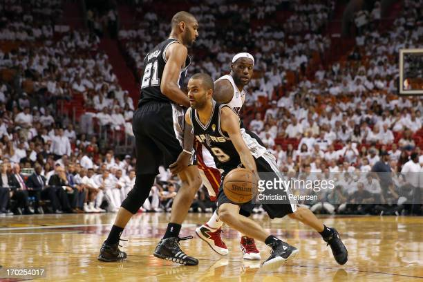 Tony Parker of the San Antonio Spurs uses a screen from Tim Duncan to get around LeBron James of the Miami Heat in the third quarter during Game Two...