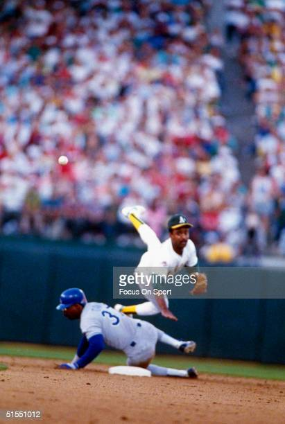 Tony Phillips of the Oakland Athletics jumps and throws over sliding Mike Davis of the Los Angeles Dodgers in a play at second base during the World...
