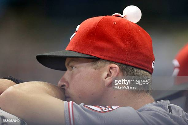 Tony Renda of the Cincinnati Reds sits in the dugout with a bubble of gum on his hat during the second inning against the Milwaukee Brewers at Miller...