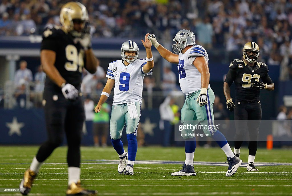 Tony Romo #9 of the Dallas Cowboys celebrates with Doug Free #68 of the Dallas Cowboys as the Cowboys take on the New Orleans Saints in the second half at AT&T Stadium on September 28, 2014 in Arlington, Texas.