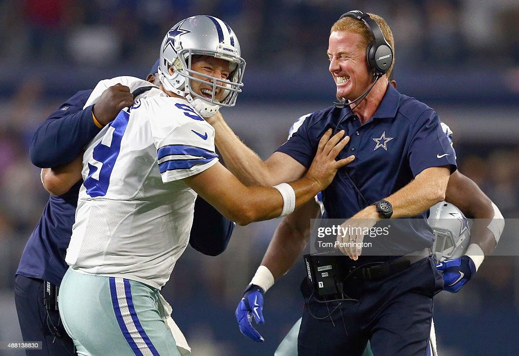 Tony Romo of the Dallas Cowboys celebrates with head coach Jason Garrett of the Dallas Cowboys after scoring the game winning touchdown against the...