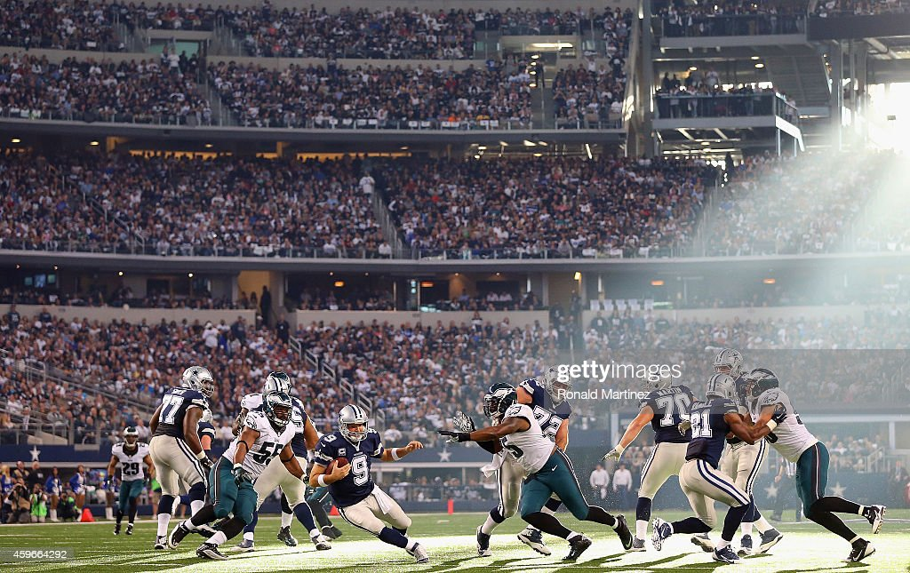 Tony Romo of the Dallas Cowboys holds the ball under pressure from the Philadelphia Eagles at Cowboys Stadium on November 27 2014 in Arlington Texas