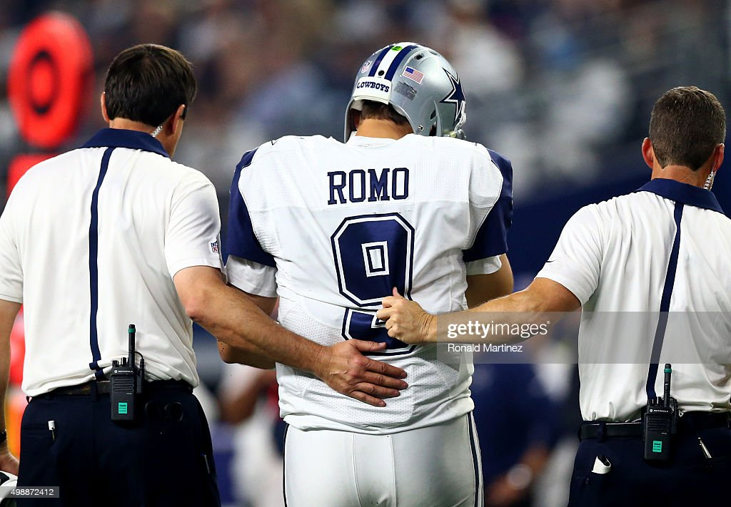 Tony Romo #9 of the Dallas Cowboys is lead to the sidelines by team officials after being sacked by the Carolina Panthers in the third quarter at AT&T Stadium on November 26, 2015 in Arlington, Texas. Romo left the field following the play.