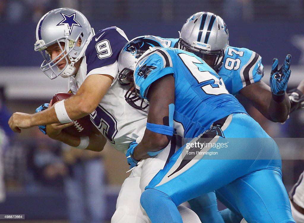 Tony Romo #9 of the Dallas Cowboys is sacked by Thomas Davis #58 and Mario Addison #97 of the Carolina Panthers in the third quarter at AT&T Stadium on November 26, 2015 in Arlington, Texas. Romo left the game after being injured on the play.