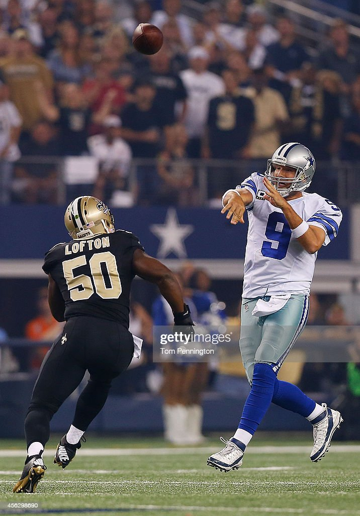 Tony Romo #9 of the Dallas Cowboys passes as Curtis Lofton #50 of the New Orleans Saints rushes in the first half at AT&T Stadium on September 28, 2014 in Arlington, Texas.