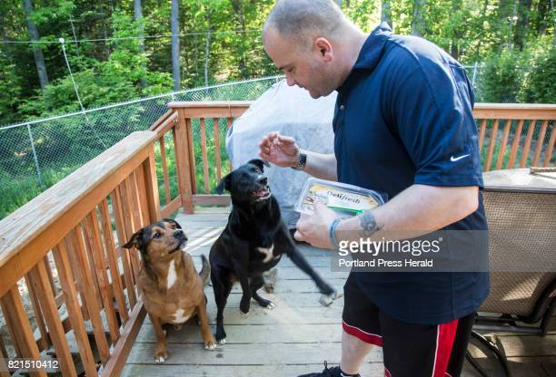 Tony Sanborn gives snacks to his dogs at his home in Westbrook on Wednesday June 7 2017