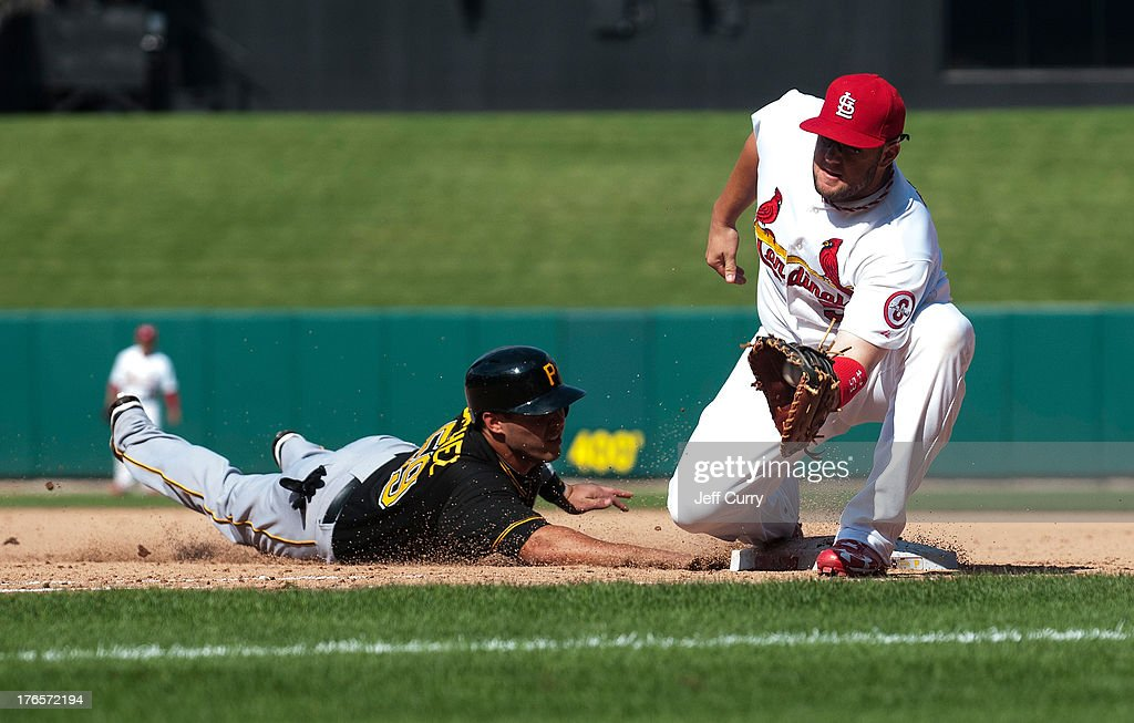 Tony Sanchez #59 of the Pittsburgh Pirates slides into first base as Matt Adams #53 of the St. Louis Cardinals takes the pick-off attempt from catcher Yadier Molina (not pictured) at Busch Stadium on August 15, 2013 in St. Louis, Missouri. Cardinals won 6-5 in twelve innings.