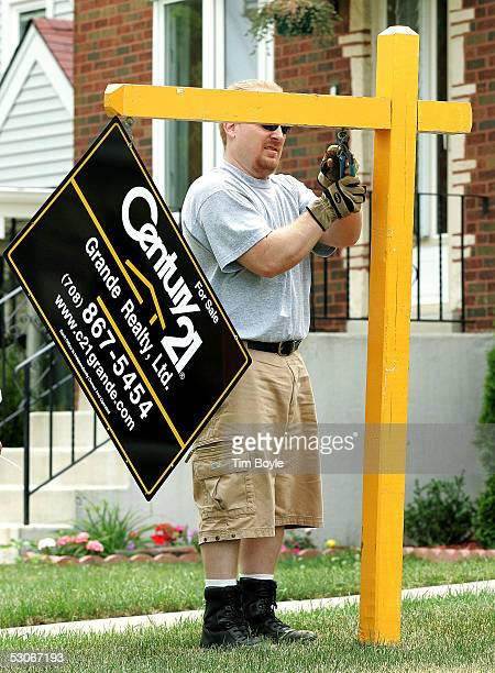 Tony Schmidt general manager of the McHenry Illinoisbased company Sign Up Sign Company installs a Century 21 'For Sale' sign in front of a home June...