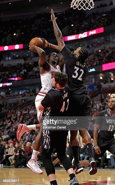 Tony Snell of the Chicago Bulls charges into Kevin Love and Ronny Turiaf of the Minnesota Timberwolves at the United Center on January 27 2014 in...