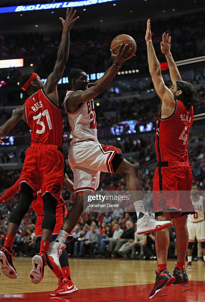 Tony Snell #20 of the Chicago Bulls drives for a shot bewteen Terrence Ross #31 and Luis Scola #4 of the Toronto Raptors at the United Center on December 28, 2015 in Chicago, Illinois. The Bulls defeated the Raptors 104-97.