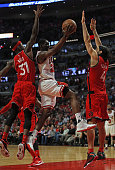Tony Snell of the Chicago Bulls drives for a shot bewteen Terrence Ross and Luis Scola of the Toronto Raptors at the United Center on December 28...