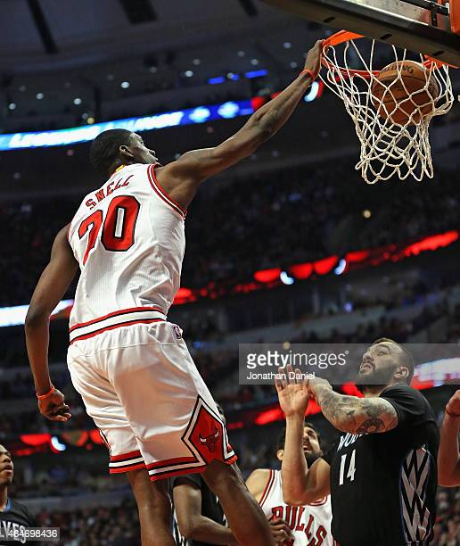 Tony Snell of the Chicago Bulls dunks over Nikola Pekovic of the Minnesota Timberwolves at the United Center on February 27 2015 in Chicago Illinois...