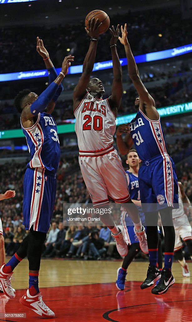 <a gi-track='captionPersonalityLinkClicked' href=/galleries/search?phrase=Tony+Snell&family=editorial&specificpeople=7551553 ng-click='$event.stopPropagation()'>Tony Snell</a> #20 of the Chicago Bulls gets off a shot between <a gi-track='captionPersonalityLinkClicked' href=/galleries/search?phrase=Robert+Covington&family=editorial&specificpeople=8607800 ng-click='$event.stopPropagation()'>Robert Covington</a> #33 and <a gi-track='captionPersonalityLinkClicked' href=/galleries/search?phrase=Hollis+Thompson&family=editorial&specificpeople=6586021 ng-click='$event.stopPropagation()'>Hollis Thompson</a> #31 of the Philadelphia 76ers at the United Center on December 14, 2015 in Chicago, Illinois. The Bulls defeated the 76ers 115-96.