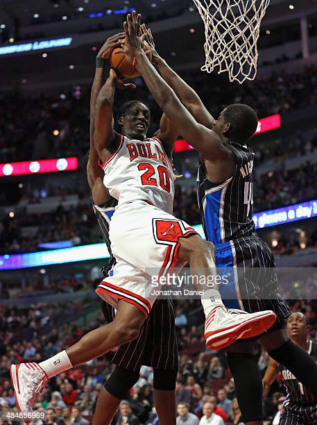 Tony Snell of the Chicago Bulls is fouled as he tries to shoot between Dewayne Dodmon and Andrew Nicholson of the Orlando Magic at the United Center...