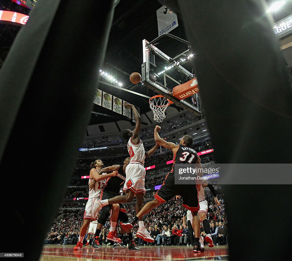 <a gi-track='captionPersonalityLinkClicked' href=/galleries/search?phrase=Tony+Snell&family=editorial&specificpeople=7551553 ng-click='$event.stopPropagation()'>Tony Snell</a> #20 of the Chicago Bulls puts up a shot over <a gi-track='captionPersonalityLinkClicked' href=/galleries/search?phrase=Shane+Battier&family=editorial&specificpeople=201814 ng-click='$event.stopPropagation()'>Shane Battier</a> #31 of the Miami Heat as seen through the referee's legs at the United Center on December 5, 2013 in Chicago, Illinois. The Bulls defeated the Heat 107-87.