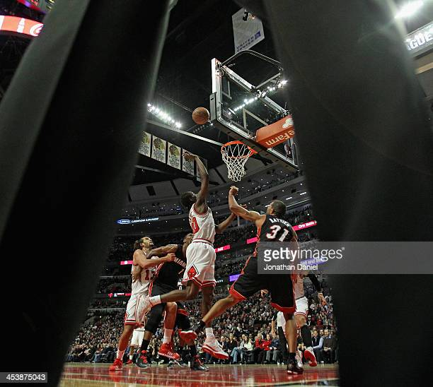 Tony Snell of the Chicago Bulls puts up a shot over Shane Battier of the Miami Heat as seen through the referee's legs at the United Center on...