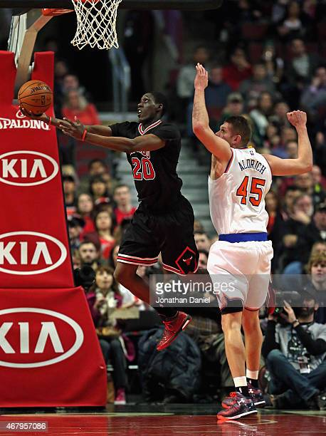 Tony Snell of the Chicago Bulls puts up a shot past Cole Aldrich of the New York Knicks at the United Center on March 28 2015 in Chicago Illinois...