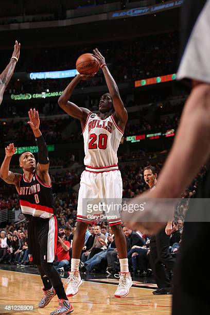 Tony Snell of the Chicago Bulls shoots past Damian Lillard of the Portland Trail Blazers on March 28 2014 at the United Center in Chicago Illinois...