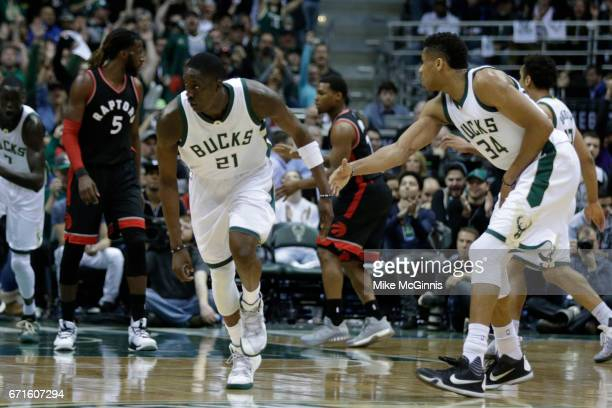 Tony Snell of the Milwaukee Bucks celebrates with Giannis Antetokounmpo a three pointer with DeMar DeRozan of the Toronto Raptors during the second...