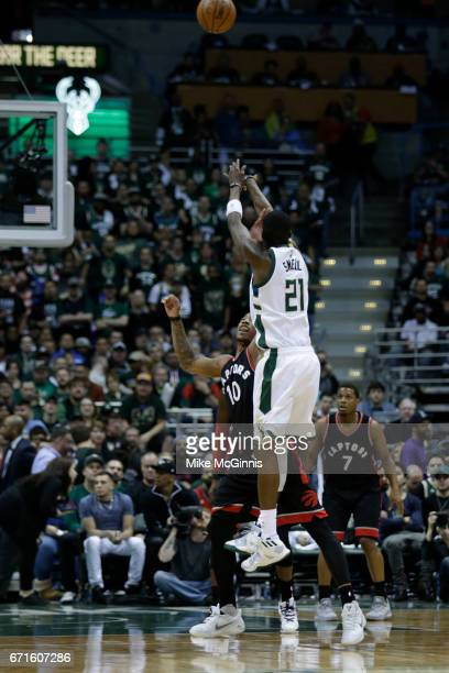 Tony Snell of the Milwaukee Bucks shoots a three pointer with DeMar DeRozan of the Toronto Raptors during the second half of Game Four of the Eastern...