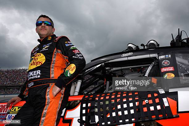 Tony Stewart driver of the Bass Pro Shops Chevrolet stands on the grid prior to the NASCAR Sprint Cup Series GEICO 500 at Talladega Superspeedway on...