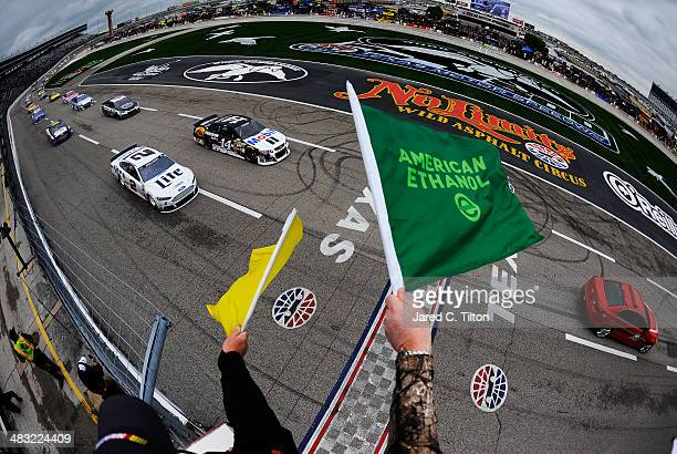 Tony Stewart driver of the Bass Pro Shops / Mobil 1 Chevrolet and Brad Keselowski driver of the Miller Lite Ford lead the field past the green and...