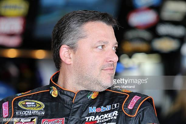 Tony Stewart driver of the Bass Pro Shops/Mobil 1 Chevrolet stands in the garage area during practice for the NASCAR Sprint Cup Series CheezIt 355 at...