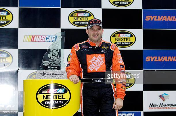 Tony Stewart driver of the Chevrole poses for photos with the trophy after winning the NASCAR Nextel Cup Series New England 300 on July 17 2005 at...