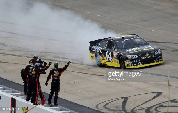 Tony Stewart driver of the Code 3 Associates/Mobil 1 Chevrolet celebrates with a burnout in front of his crew after winning the NASCAR Sprint Cup...