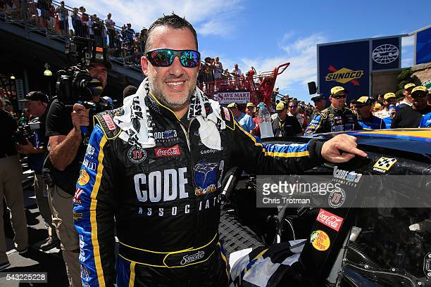 Tony Stewart driver of the Code 3 Assoc/Mobil 1 Chevrolet applies a Winner Sticker in victory lane after winning the NASCAR Sprint Cup Series...