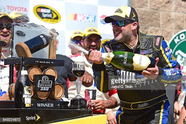 Tony Stewart driver of the Code 3 Assoc/Mobil 1 Chevrolet celebrates with champagne in victory lane after winning the NASCAR Sprint Cup Series...