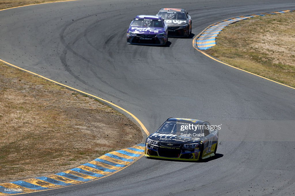 <a gi-track='captionPersonalityLinkClicked' href=/galleries/search?phrase=Tony+Stewart+-+Race+Car+Driver&family=editorial&specificpeople=201686 ng-click='$event.stopPropagation()'>Tony Stewart</a>, driver of the #14 Code 3 Assoc/Mobil 1 Chevrolet, leads <a gi-track='captionPersonalityLinkClicked' href=/galleries/search?phrase=Denny+Hamlin&family=editorial&specificpeople=504674 ng-click='$event.stopPropagation()'>Denny Hamlin</a>, driver of the #11 FedEx Cares Toyota, during the NASCAR Sprint Cup Series Toyota/Save Mart 350 at Sonoma Raceway on June 26, 2016 in Sonoma, California.