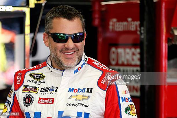 Tony Stewart driver of the Haas Automation Chevrolet stands in the garage area during practice for the NASCAR Sprint Cup Series New Hampshire 301 at...