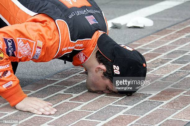 Tony Stewart driver of the Home Depot Chevrolet does the traditional kissing of the bricks after winning the NASCAR Nextel Cup Series Allstate 400 at...
