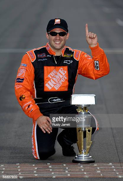 Tony Stewart driver of the Home Depot Chevrolet poses with the trophy on the famous tard of bricks after winning the NASCAR Nextel Cup Series...