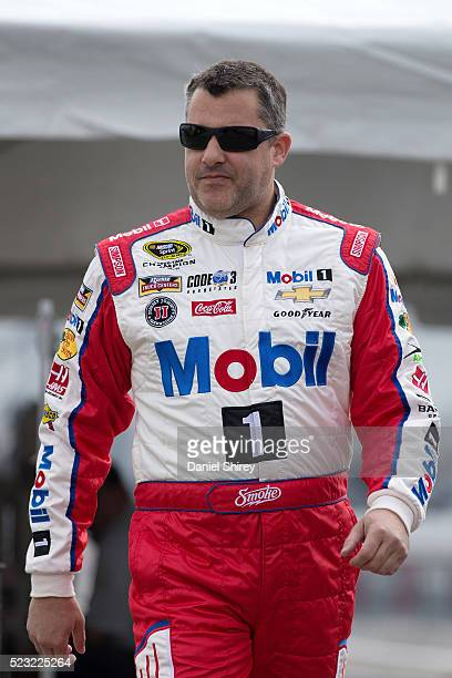 Tony Stewart driver of the Mobil 1 Advanced Fuel Economy Chevrolet stands in the garage area during practice for the NASCAR Sprint Cup Series TOYOTA...