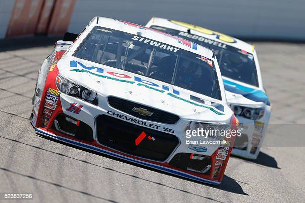 Tony Stewart driver of the Mobil 1 Advanced Fuel Economy Chevrolet races Michael McDowell driver of the WRL General Contractors Chevrolet during the...