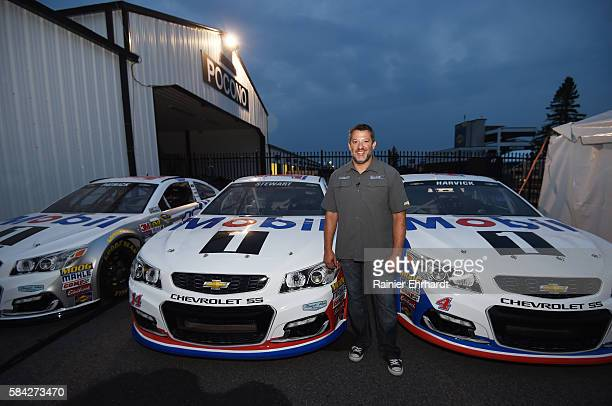 Tony Stewart driver of the Mobil 1 Chevrolet poses in front of the StewartHaas Racing cars during a Mobil 1 and iRacing event at Pocono Raceway on...