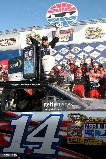 Tony Stewart driver of the Mobil 1/Office Depot Chevrolet celebrates with his crew in victory lane after he won the Sylvania 300 at the New Hampshire...