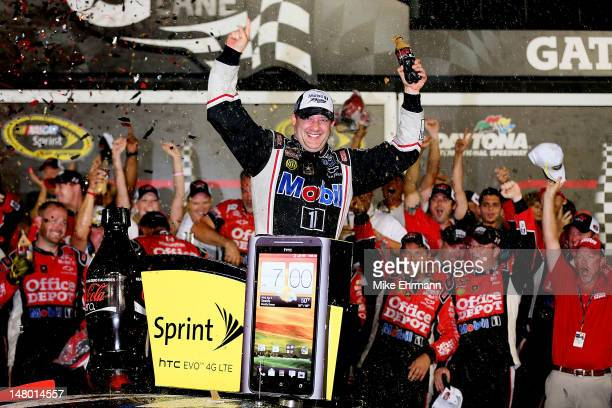 Tony Stewart driver of the Mobil 1/Office Depot Chevrolet celebrates in Victory Lane after winning the NASCAR Sprint Cup Series Coke Zero 400 Powered...