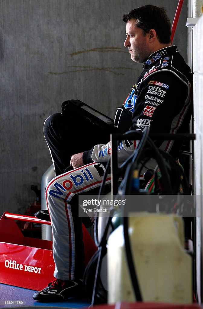 Tony Stewart, driver of the #14 Mobil 1/Office Depot Chevrolet, sits in the garage area during practice for the NASCAR Sprint Cup Series Bank of America 500 at Charlotte Motor Speedway on October 11, 2012 in Charlotte, North Carolina.