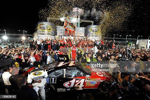 Tony Stewart driver of the Office Depot/Mobil 1 Chevrolet celebrates in Victory Lane after winning the NASCAR Sprint Cup Series Ford 400 and the 2011...