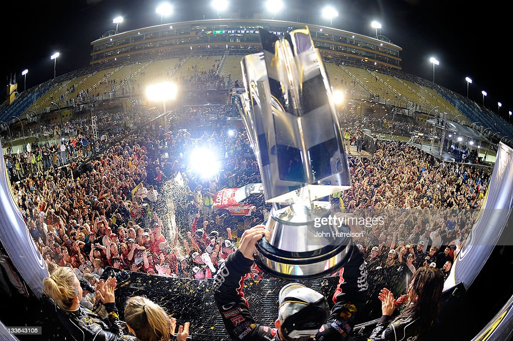 <a gi-track='captionPersonalityLinkClicked' href=/galleries/search?phrase=Tony+Stewart+-+Race+Car+Driver&family=editorial&specificpeople=201686 ng-click='$event.stopPropagation()'>Tony Stewart</a>, driver of the #14 Office Depot/Mobil 1 Chevrolet, celebrates with the trophy in Victory Lane after winning the NASCAR Sprint Cup Series Ford 400 and the 2011 Series Championship at Homestead-Miami Speedway on November 20, 2011 in Homestead, Florida. Stewart wins his third NASCAR Championship.